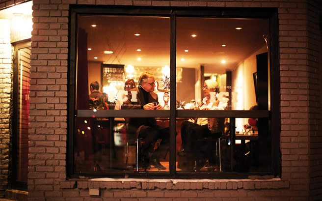 Nighttime exterior of a busy Ici Bistro