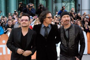 Bono, David Guggenheim and The Edge pose for pictures.
