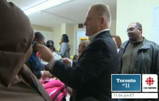 Doug Ford hands out $20 bills to residents of a social-housing complex in his ward. (Image: Screenshot/CBC)