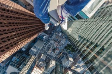 Ronnie Yip's feet dangle from a Toronto rooftop