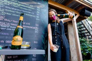 A masked woman pours an alcohol from a bottle into a cup