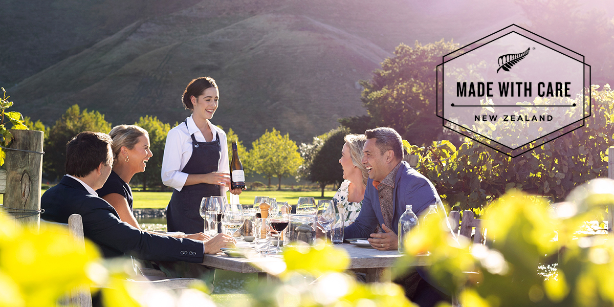 People sitting at a table on a vineyard