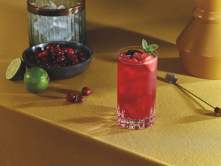 A fruity cocktail sits on a yellow table with a blow of cranberries in the background